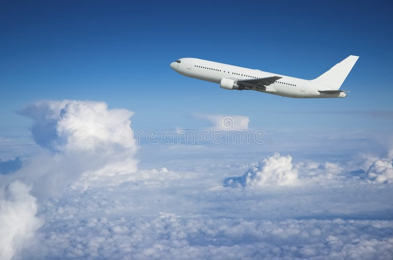 Airliner climbing above the cl royalty free stock image