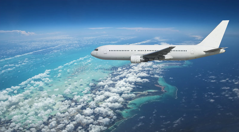 Airliner over exotic island royalty free stock photography