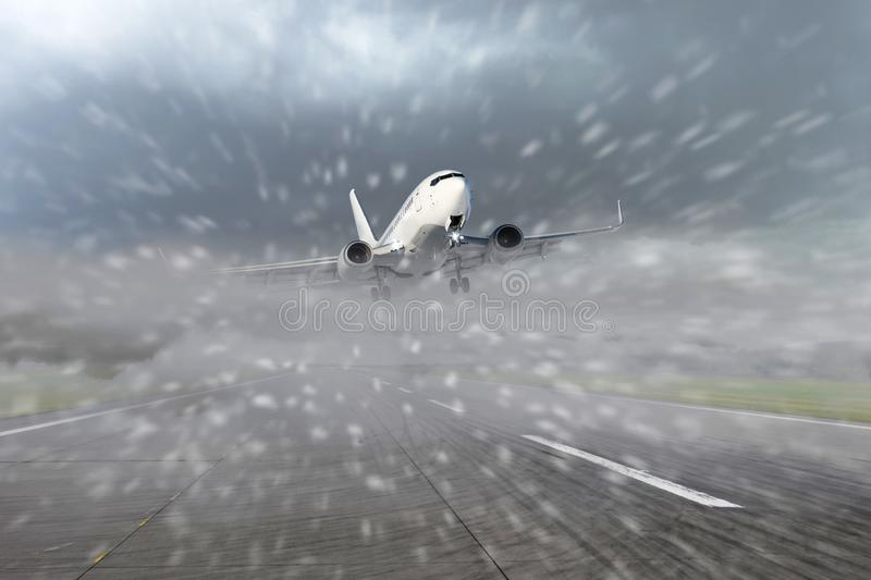 Airliner taking off from the runway at the airport during bad weather, low visibility, snow. Concept of delayed or late flights.  royalty free stock images