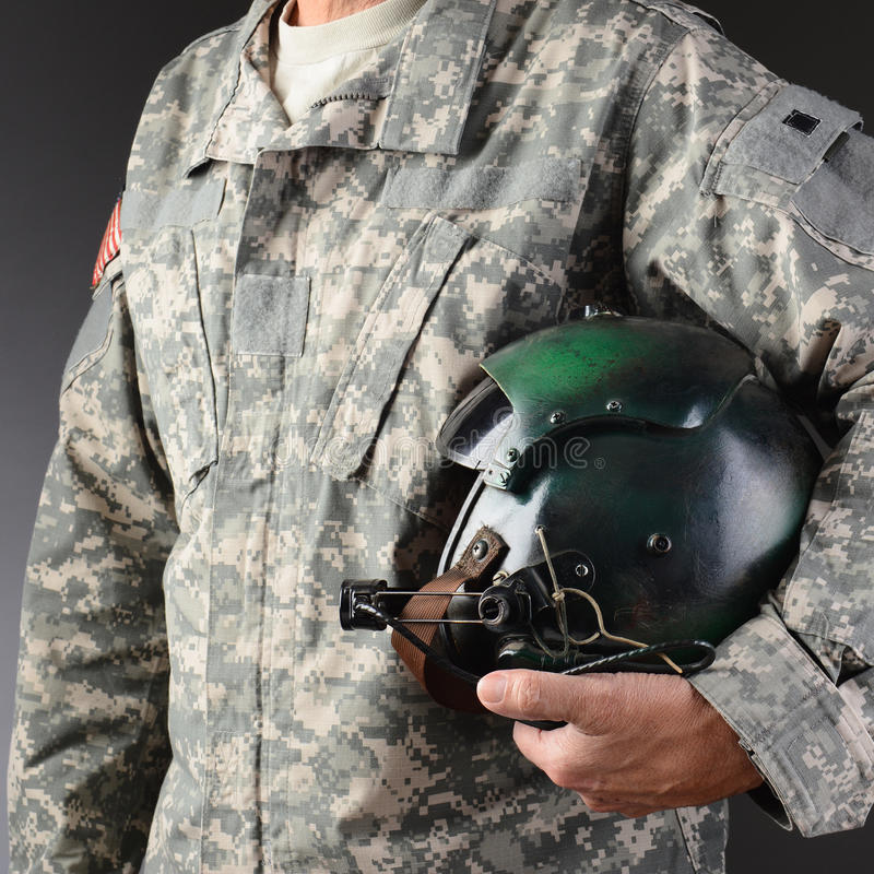 Airman With Flight Helmet. Closeup of an American Airman in camouflage fatigues holding a flight helmet under one arm, Square format, man is unrecognizable stock image