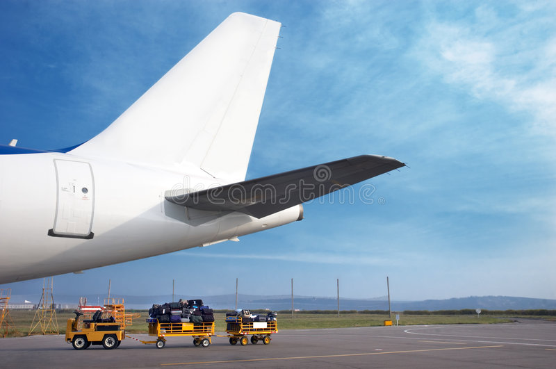 Airplain tail and luggage cart stock photos