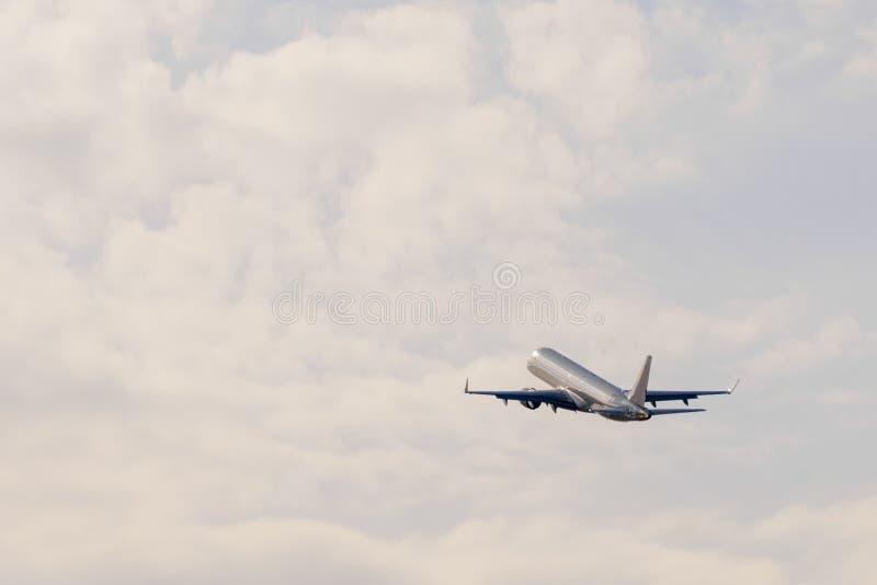 Airplan iść w kierunku chmur przy zmierzchem po zdejmuje zdjęcie stock