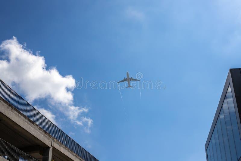 Airplan opuszcza ślad w niebieskim niebie Samolot takking daleko nad budować i mostem Biel chmura w błękicie fotografia stock