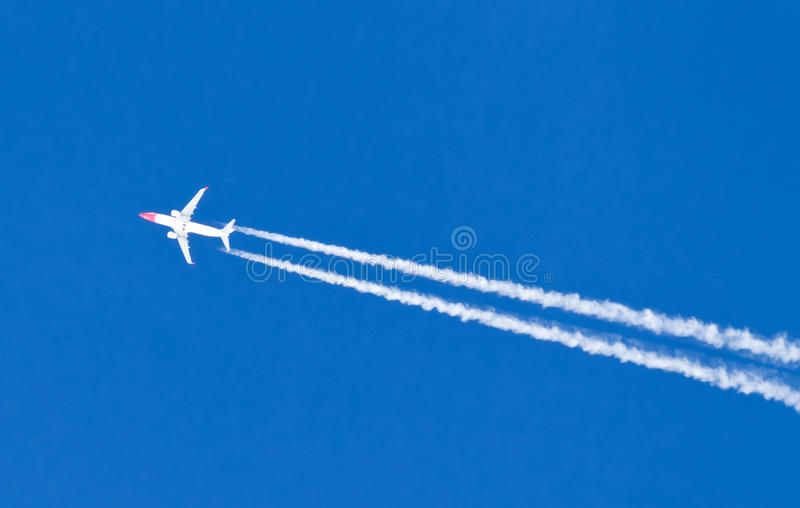 Airplane. With condensation tail isolated on blue sky royalty free stock photography