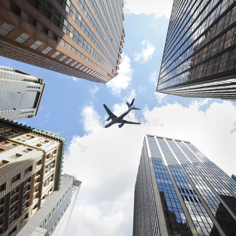 Airplane Passenger plane / aircraft flying over and between skyscrapers  royalty free stock image