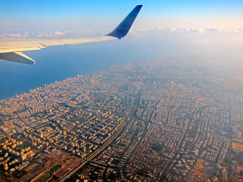 Airplane above city. An airplane above a city and ocean early in the morning stock images