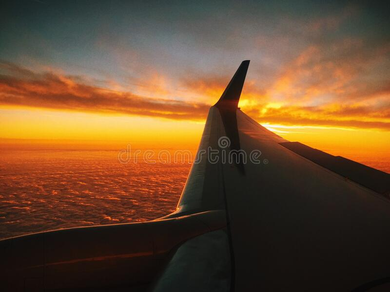 Airplane above sea at sunset royalty free stock photography