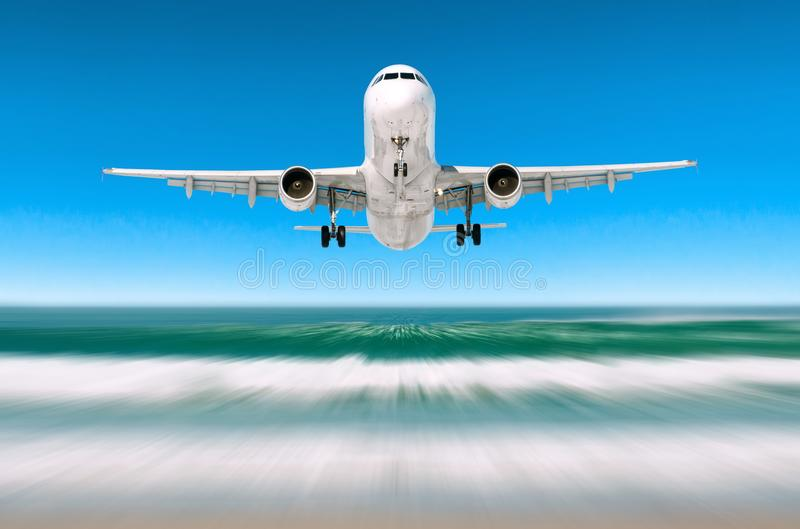 Airplane above tropical sea at comes flying over the beach before boarding the airport. royalty free stock photo