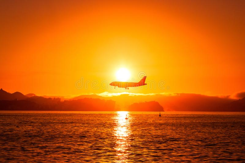Airplane Above Water by Sunset stock photo