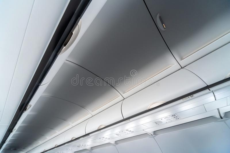 Airplane air conditioning control panel over seats. Stuffy air in aircraft cabin with people. New low-cost airline stock image