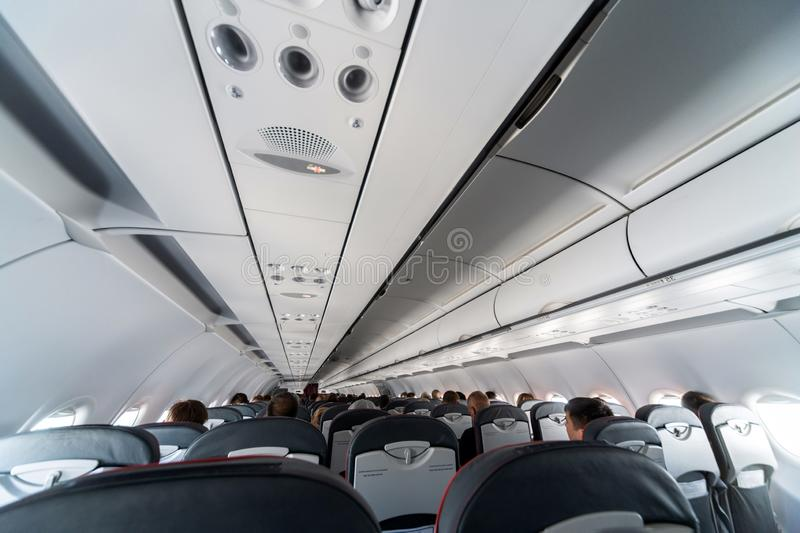 Airplane air conditioning control panel over seats. Stuffy air in aircraft cabin with people. New low-cost airline stock photography