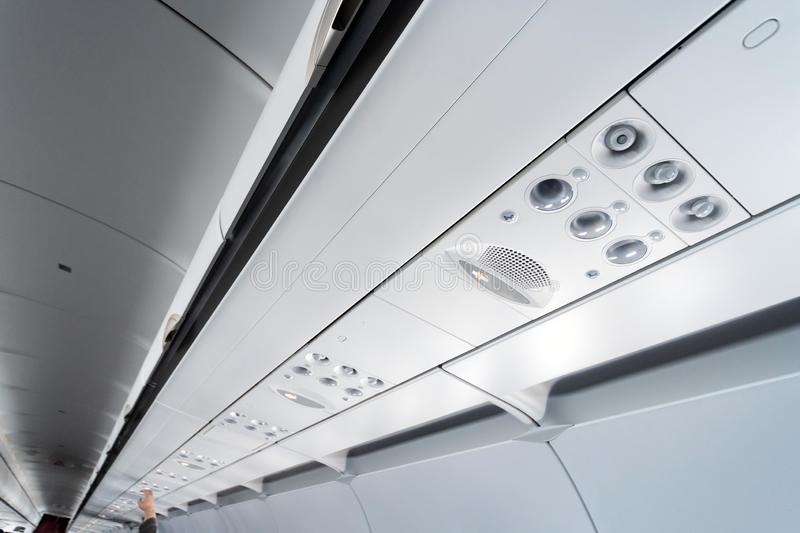 Airplane air conditioning control panel over seats. Stuffy air in aircraft cabin with people. New low-cost airline stock photos