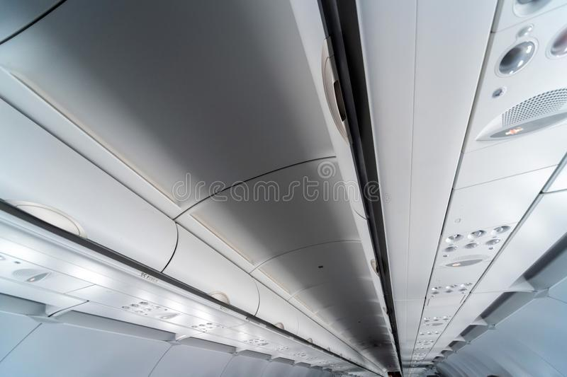 Airplane air conditioning control panel over seats. Stuffy air in aircraft cabin with people. New low-cost airline royalty free stock images