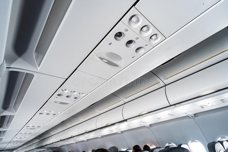 Airplane air conditioning control panel over seats. Stuffy air in aircraft cabin with people. New low-cost airline stock images