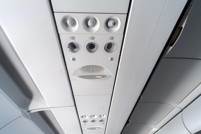 Airplane air conditioning control panel over seats. Stuffy air in aircraft cabin with people. New low-cost airline royalty free stock photography