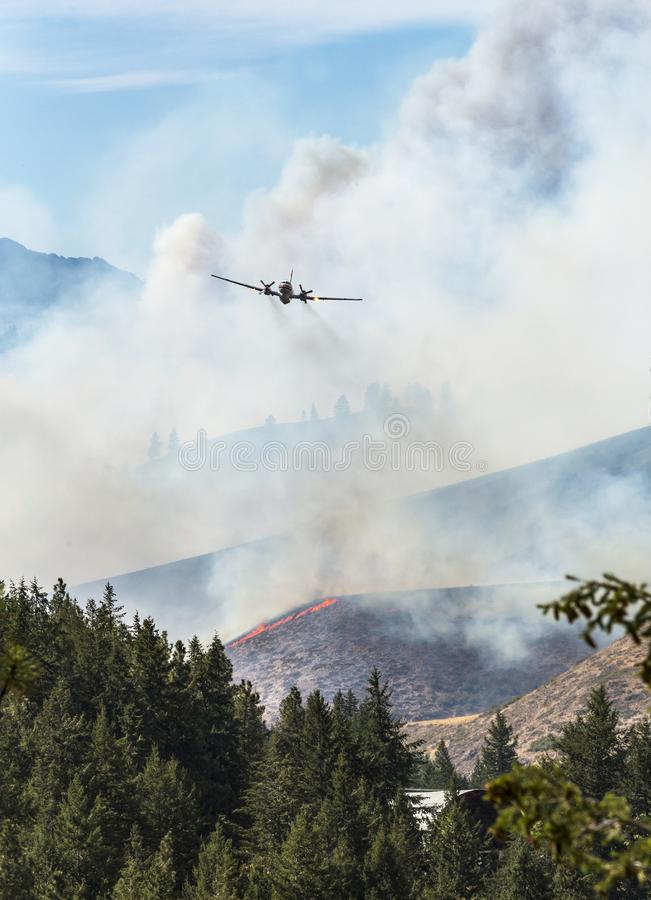 Airplane aircraft air tanker plane battling fighting wildland forest fire wildfire in Eastern Washington State. Smoke and flames. Engulf the landscape. Natural stock photography