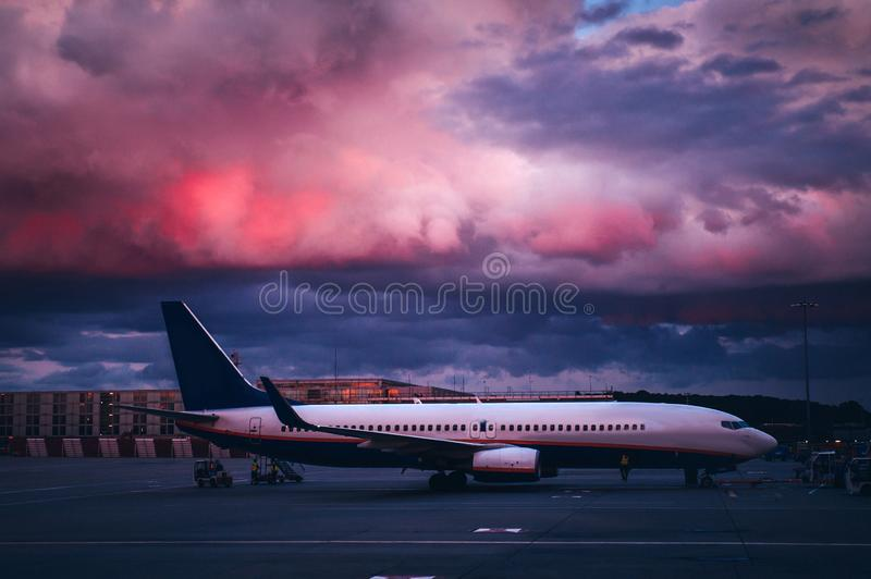 Airplane at the airport in evening. Beautiful sky in background.  royalty free stock photos