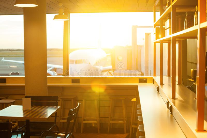 Airplane through airport window in sun light. Airport terminal background, cafe and waiting room.  stock photography