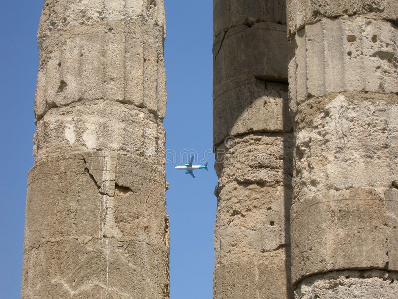 Airplane and ancient city. The airplane flying between pillars of the ancient building in Greece royalty free stock photo