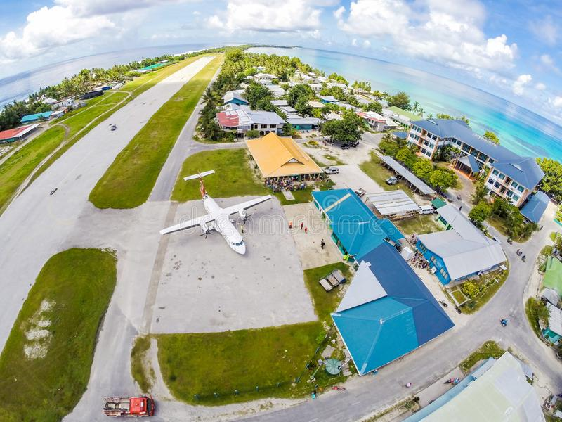 Airplane on apron of Tuvalu international airport, just arrived. Aerial view. Vaiaku village, Funafuti atoll, Polynesia, Oceania. An airplane on the apron of royalty free stock photography