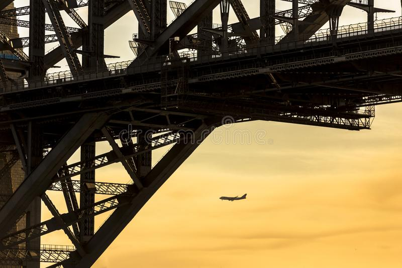 Airplane as view from beneath Sydney harbour bridge that links north and south sydney city. All basked in good evening light. Airplane as view from beneath royalty free stock photo