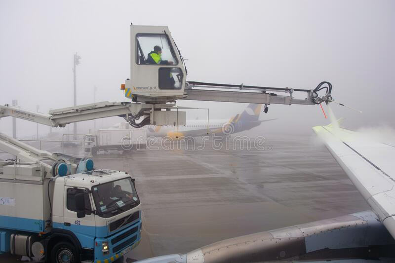 Airplane is being prepared for flight. The wing is sprayed by special liquid to prevent icing in Kyiv international airport Borysp royalty free stock images