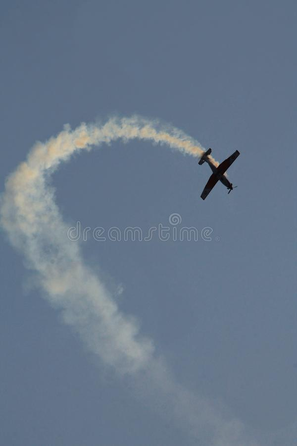 Airplane in blue sky fly make loop and crash.  stock photography