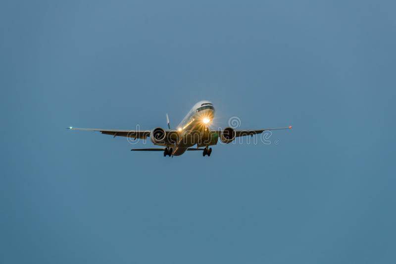 Airplane in the blue sky at night with head light. Toward to the front stock photos