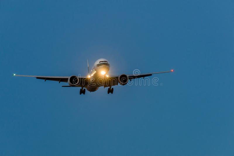 Airplane in the blue sky at night with headlight. Toward to the front royalty free stock photography
