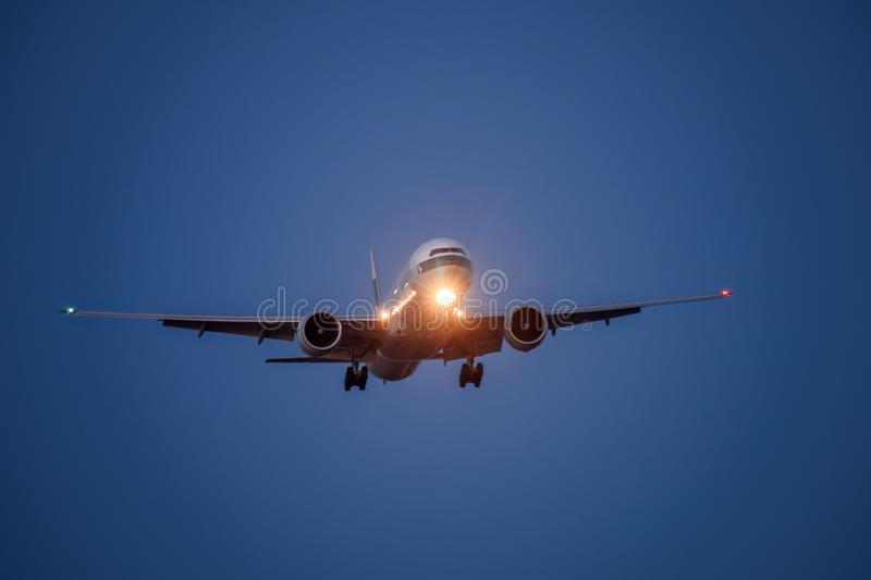 Airplane in the blue sky at night with headlight. Toward to the front royalty free stock photos
