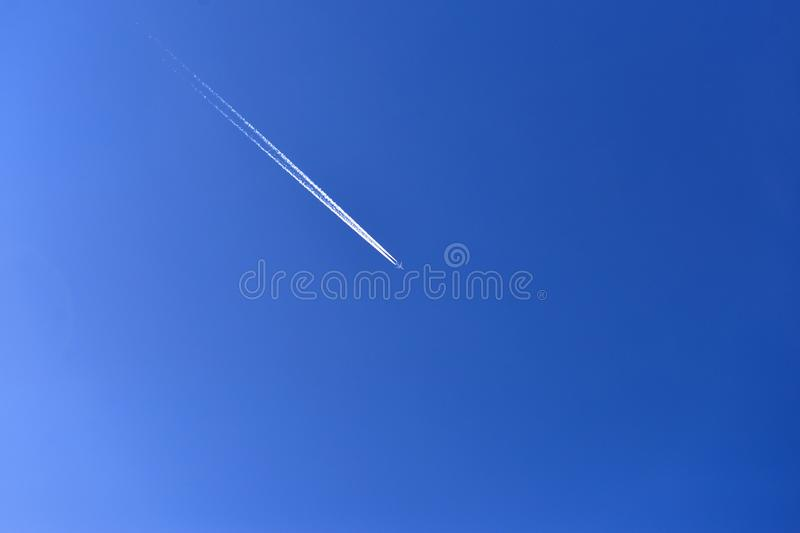 Airplane in the blue sky. Trace of an airplane in the sky during the day. stock images