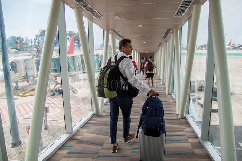 Casual male passenger carrying the hand luggage bag, walking the airplane boarding corridor. royalty free stock photography