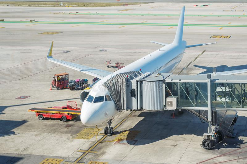 Airplane at boarding gate. White airplane at boarding gate by bright sunny day royalty free stock photography