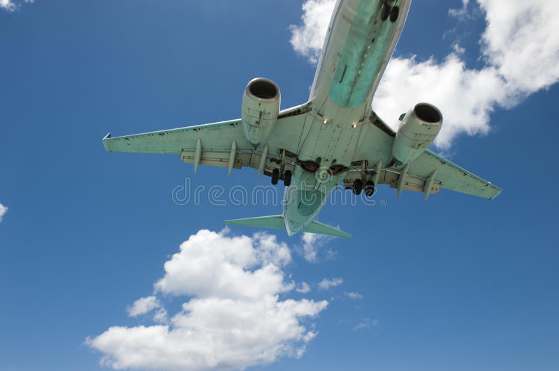 Airplane Bottom. An airplane propelling past camera frame, making it able to capture a bottom shot of the vehicle in motion royalty free stock image