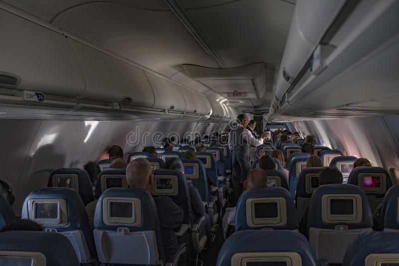 Airplane cabin. Seattle-Chicago - October 23, 2019: Flight attendants doing the drink and snack service on the domestic flight royalty free stock images