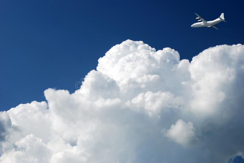 Airplane in the clouds stock photography