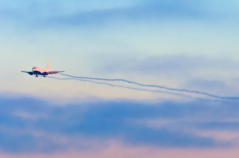 Airplane comes in approach at the airport before landing through the clouds at sunset stock photos