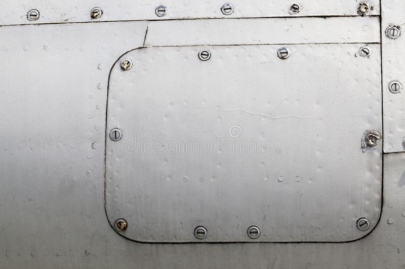 Airplane cover. Part of the metal structure made of a sheet of gray aluminum with rivets, the surface formed by corrosion and rust, Airplane airframe close-up stock photos
