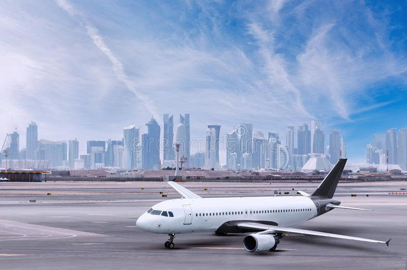 Airplane at Doha airport, cityscape view with skyscrapers in background. stock photos