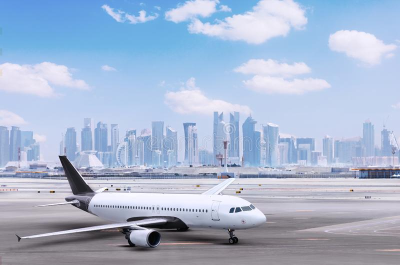 Airplane at Doha airport, cityscape view with skyscrapers in background. royalty free stock photography