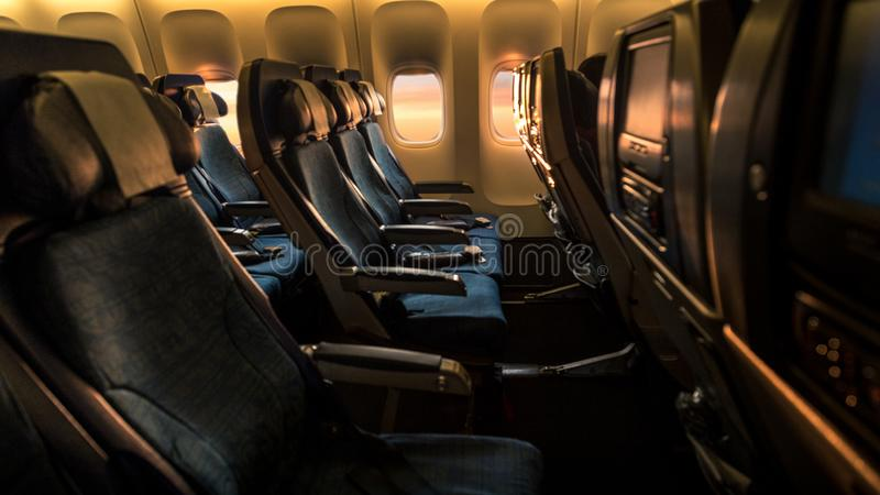 Airplane empty cabin with a beautiful sunset orange light royalty free stock image