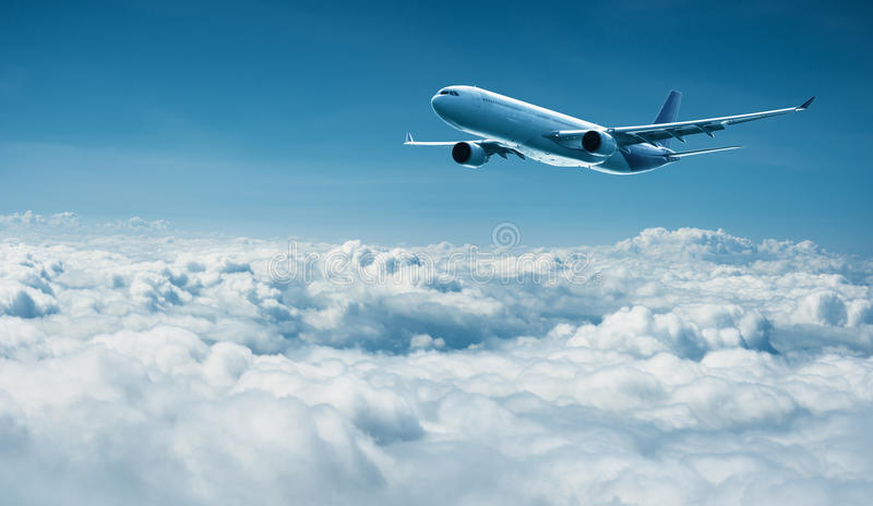 Airplane flies above clouds - air travel royalty free stock image
