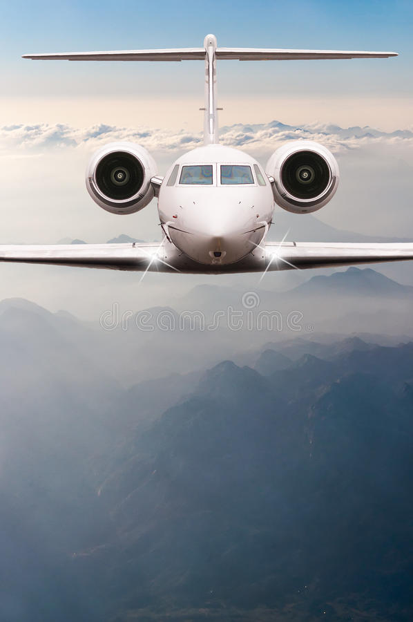 Airplane fly over clouds and Alps mountain on sunset. Front view of a big passenger or cargo aircraft, business jet stock photography