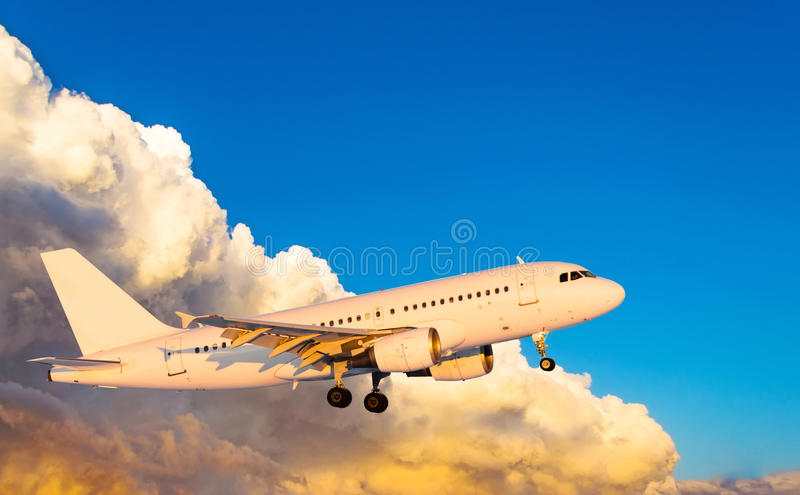 Airplane at fly on the sky with clouds sunset royalty free stock photography