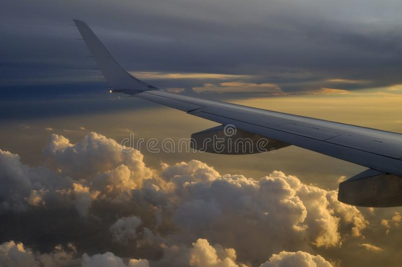 Airplane flying above the clouds against a beautiful sunset royalty free stock images