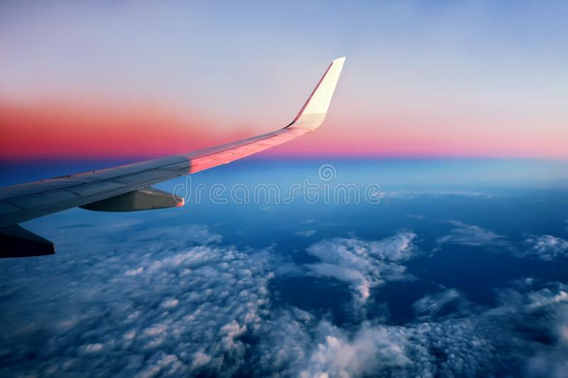 Airplane flying above clouds at pink sunrise stock photo
