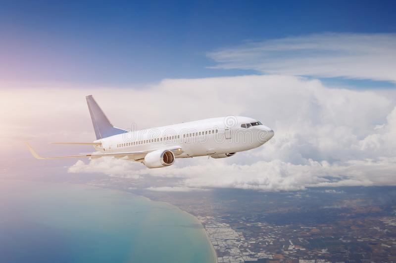 Airplane is flying above the day clouds, travel trip vacation stock image