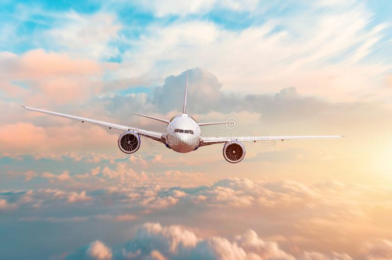 Airplane flying above evening light above the clouds at sunset.  stock image