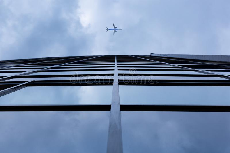 Airplane flying above modern architecture glass office building stock image
