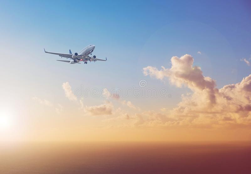 Airplane flying above ocean with sunset sky background - trav stock photos